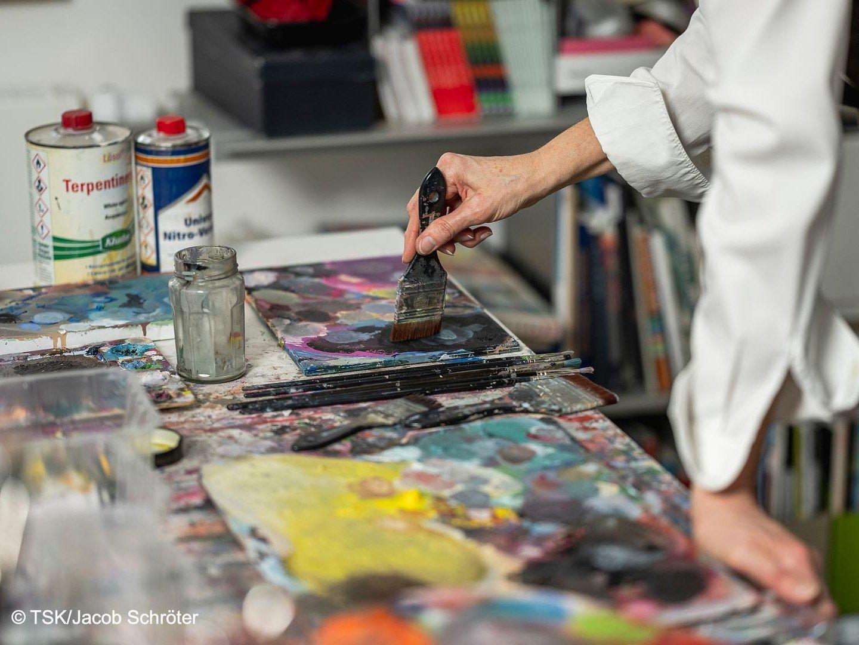 Clivia Bauer in ihrem Atelier, Hand mit Pinsel malt, umgeben von Utensilien