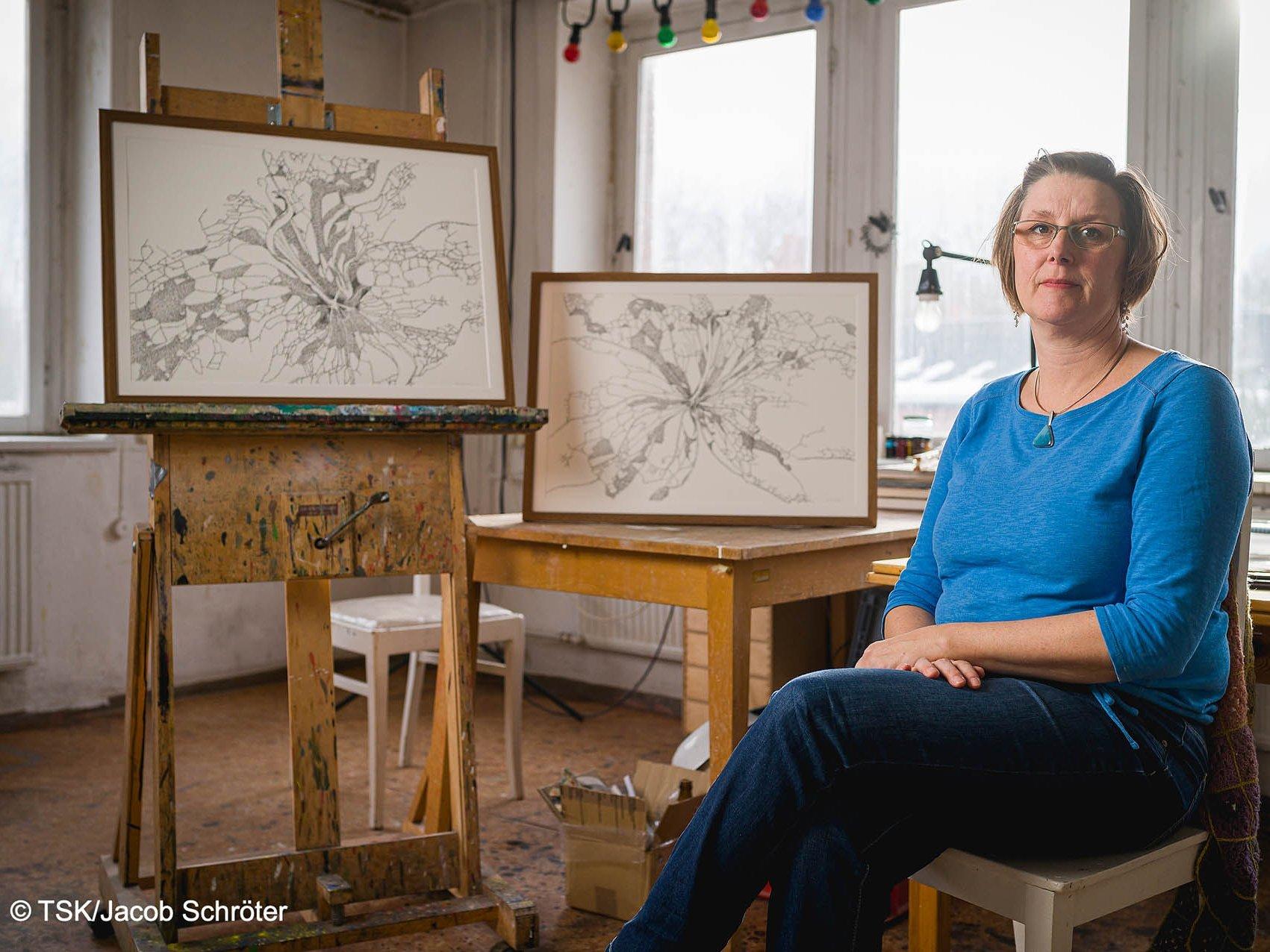 """Die Künstlerin Nina Lundström sitzt neben ihren ausgestellten Zeichnungen """"Zwischenheit I"""" und """"Zwischenheit II"""""""
