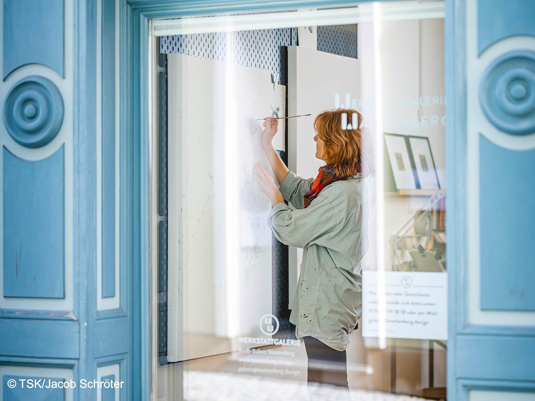 Die Künstlerin Steffi-Babett Wartenberg malt in ihrem Atelier, durch das Schaufenster fotografiert