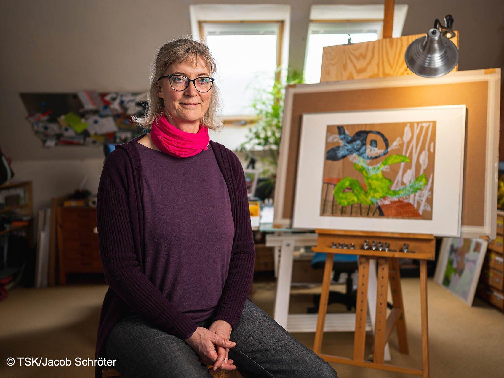 """Die Künstlerin Sibylle Reichel neben ihrem Werk """"Bezeugung einer fröhlichen Transformation"""""""
