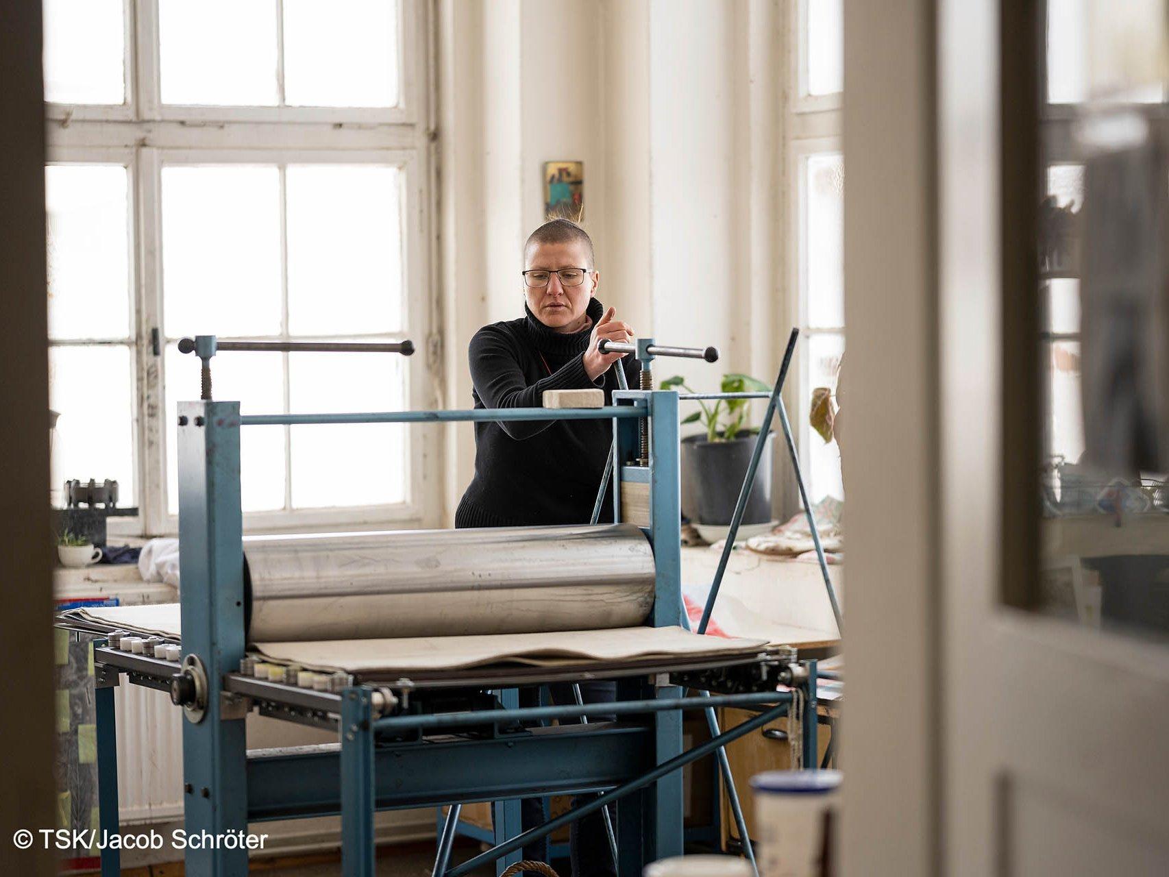 Die Künstlerin Tanja Pohl arbeitet in ihrem Atelier an einer Druckerpresse