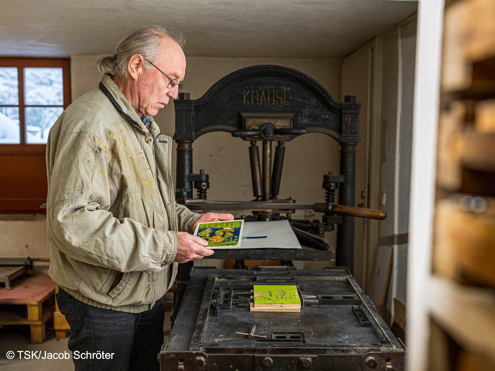 Der Künstler Martin Max beim Anfertigen eines Druckes mit einer alten Offset-Druckpresse