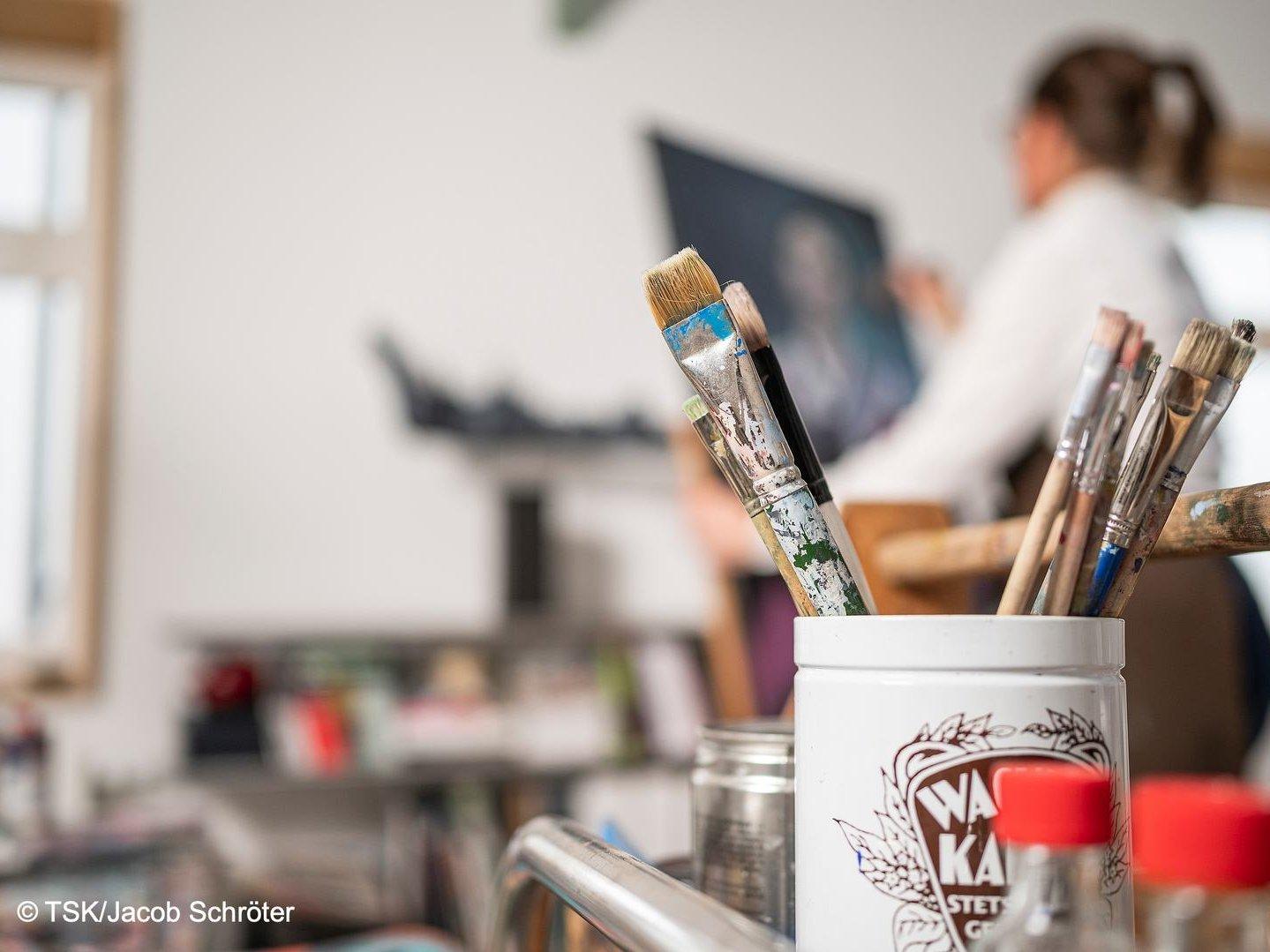 Clivia Bauer in ihrem Atelier, im Vordergrund Materialien zum Malen, Pinsel und Farbe