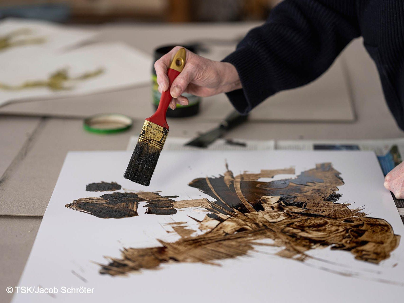 Nahaufnahme der Hand der Künstlerin Heike Stephan, die ein Bild mit einem groben Malerpinsel malt