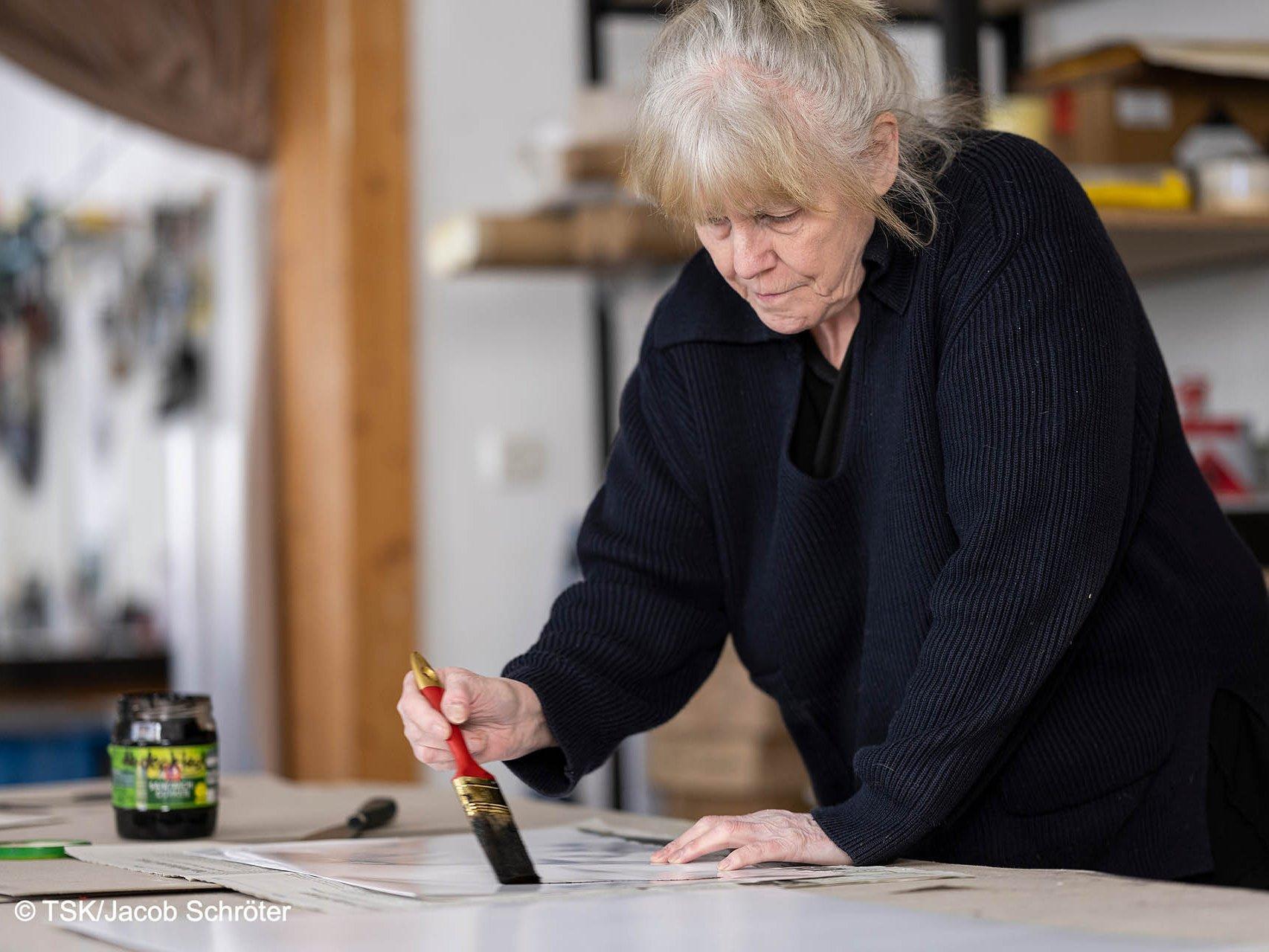 Heike Stephan erschafft ein neues Werk in ihrem Atelier mit einem groben Malerpinsel