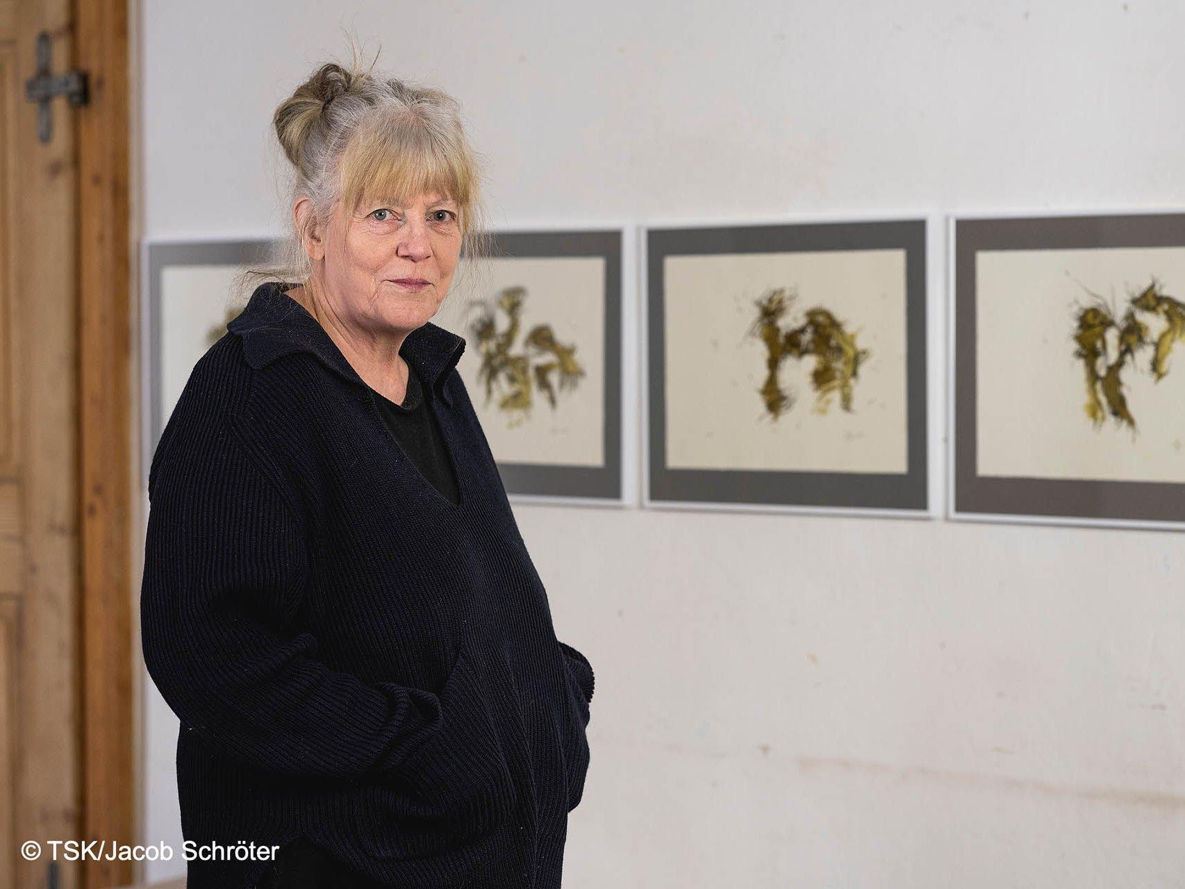 """Heike Stephan stehend neben ihrer Bilder-Serie """"Orakel - Spektakel"""" an der Wand"""
