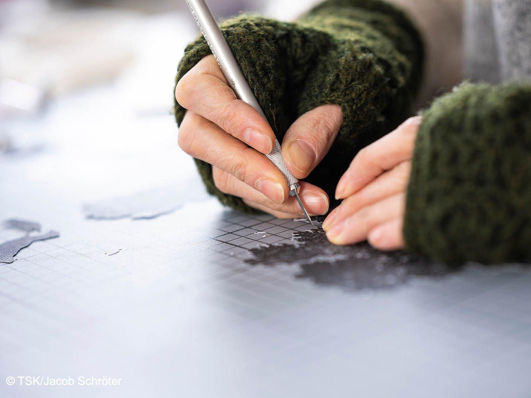 Nahaufnahme der Hände der Künstlerin Sophie von Hayek, die gerade mit einem Skalpell ein Bild ausschneidet