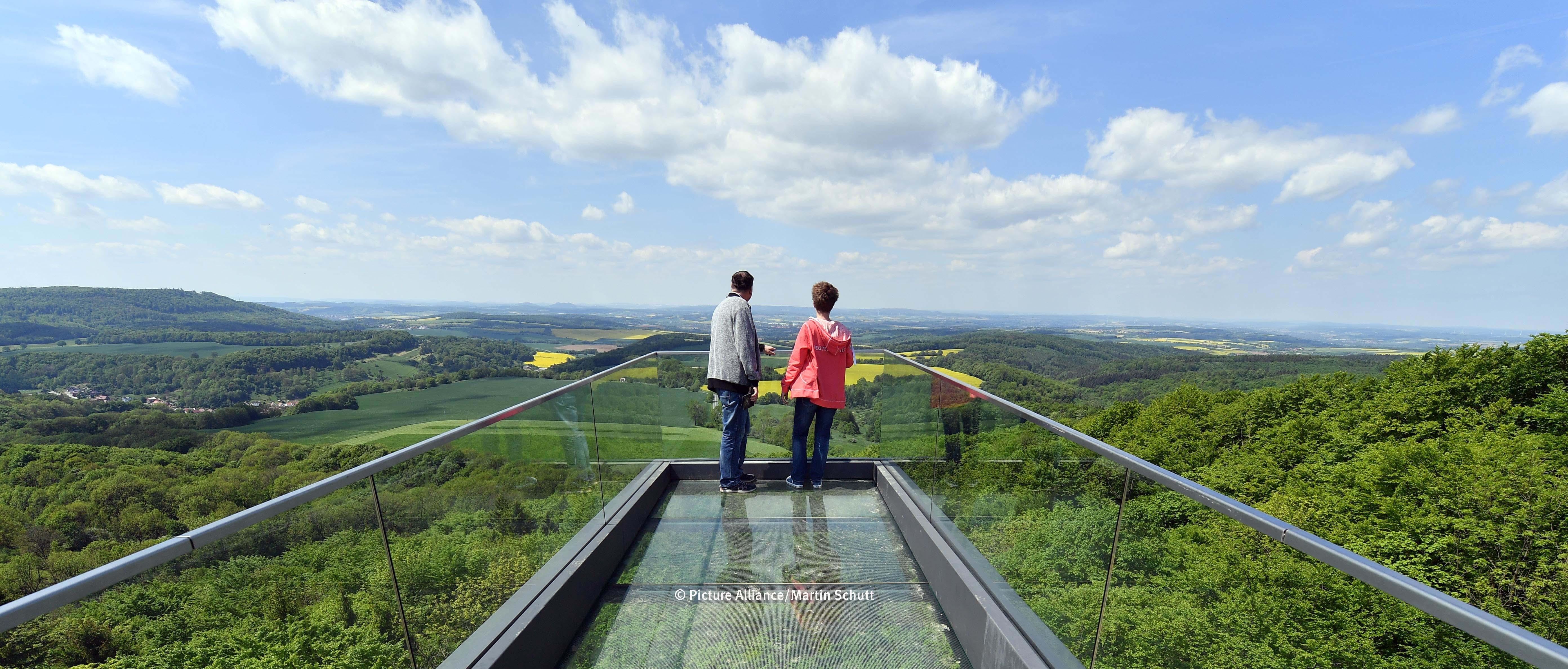 Ein Paar blickt vom Skywallk auf die sommerliche Landschaft Thüringens